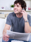 Man with phone reading newspaper Stock Photo
