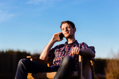 Man with Phone Relaxing by a Lake in Forest.  Royalty Free Stock Photo