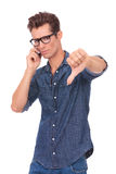 Man on the phone shows thumb down. Casual young man receiving some bad news over the phone and showing thumbs down. isolated on a white background Royalty Free Stock Image