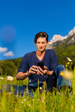 Man with phone  sitting in the mountains Stock Image