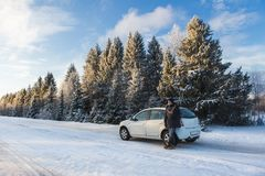 A man with a phone is standing by the car. On a winter road Royalty Free Stock Photography
