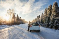 A man with a phone is standing by the car. On a winter road Stock Images