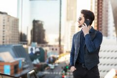 A man on the phone: strategical phone call on the balcony overlooking busy financial city center. stock photo