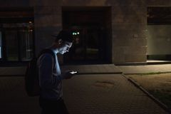 The man phone on the street. Evening night time. Street lights. Telephoto lens shot.  royalty free stock photos