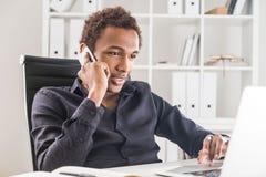 Man on phone using laptop Royalty Free Stock Photos