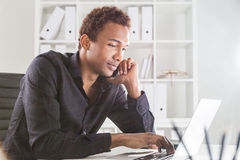 Man on phone using notebook Stock Photo