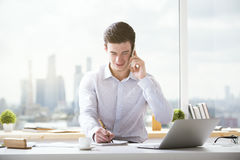 Man on phone writing. Smiling young businessman talking on mobile phone and writing something in notepad Stock Photo