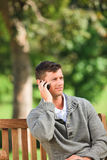 Man phoning on the bench Royalty Free Stock Photography
