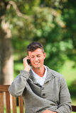 Man phoning on the bench Stock Image