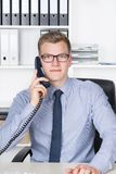 Man is phoning at the desk in the office Stock Photo