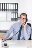 Man is phoning at the desk in the office. Young smiling businessman with glasses is phoning while sitting at the desk in the office. A shelf is in the background Royalty Free Stock Image