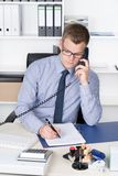 Man is phoning and making notes in a file Royalty Free Stock Photo