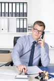 Man is phoning and typing at a desk calculator Royalty Free Stock Image