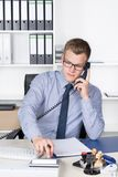 Man is phoning and typing at a desk calculator Stock Photo