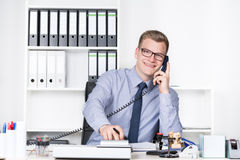Man is phoning and typing at a desk calculator Royalty Free Stock Photos