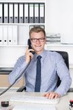 Man is phoning and typing at the keyboard Royalty Free Stock Photos