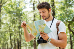 Man with photo camera standing and using map in forest Stock Image