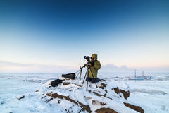 Man with photo camera on tripod taking timelapse photos in the arctic tundra. Stock Photos