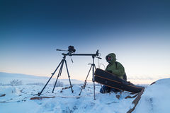 Man with photo camera on tripod taking timelapse photos in the arctic tundra. Poor lighting conditions Royalty Free Stock Image