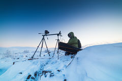 Man with photo camera on tripod taking timelapse photos in the arctic tundra. Poor lighting conditions Stock Photos