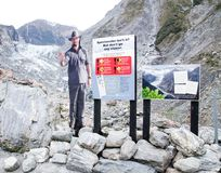 A Man photo stand shows warning sign regulation for ice fall, Rock fall, flooding, river surge at Fox Glacier. Westland Tai Poutini National Park, New Zealand`s royalty free stock photo