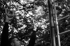 Man photographed in street workout session. Photo was taken in early morning, around 6am in city park Dudova forest. Black and white photo stock image