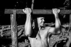Man photographed in street workout session. Working chin-ups. Photo was taken in early morning, around 6am in city park Dudova forest. Black and white photo Stock Image