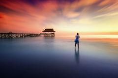 Man photographed sunset near the pier Stock Images
