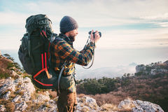 Man photographer with backpack and camera taking photo of mountains. Travel Lifestyle hobby concept adventure vacations outdoor Stock Photos
