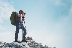 Man photographer with big backpack and camera taking photo of mountains Royalty Free Stock Images