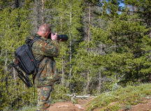Man photographer in camouflage outfit shooting, taking pictures Royalty Free Stock Image