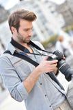 Man photographer checking photos on a reflex Royalty Free Stock Image