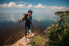 Man photographer holding his camera. Lake background Royalty Free Stock Photo