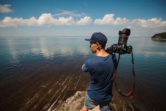 Man photographer holding his camera. Lake background Stock Image