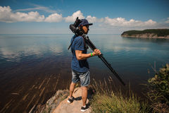 Man photographer holding his camera. Lake background Royalty Free Stock Photos