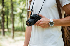 Man photographer holding modern photo camera in forest Stock Image