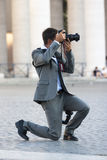 Man photographer lunges taking picture Stock Image