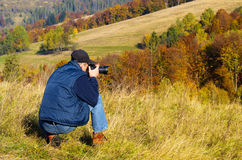 Man photographer in the mountains forest. Royalty Free Stock Photos