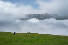 Man  photographer in the mountains on a green meadow and white clouds fog. People taking pictures in the mountains on a green meadow and white clouds fog Royalty Free Stock Photography