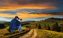 Man photographer in the mountains at sunset. Pictures of autumn landscape in front of him Royalty Free Stock Photography