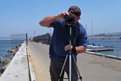 Man photographer on ocean pier. Male photographer in baseball cap is using a tripod and camera on a pier in Monterey, California Royalty Free Stock Photography