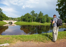 The man the photographer with a photocamera on a tripod on the bank of the lake Royalty Free Stock Images