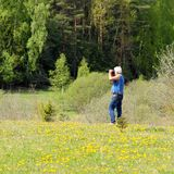 Man photographer photographing in nature. Old handsome gray-haired man photographer photographing in nature Stock Image