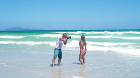 Man photographer taking photography of young woman in bikini posing on sea beach. Young man photographer working with stock video