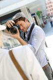 Man photographer taking photos of his model in the streets Royalty Free Stock Photo