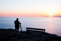 Man photographer taking photos of sunset at the sea Royalty Free Stock Photography