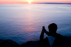 Man photographer taking photos of sunset at the sea Stock Photo