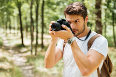 Man photographer taking pictures with modern photo camera in forest Stock Photography