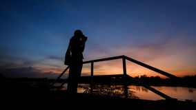 Man Photographer taking pictures sunset. Man Photographer taking pictures sunset, shooting photo for a sunset and riverside Royalty Free Stock Photos