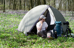 Man photographer working outdoors in a tent camp. Royalty Free Stock Image